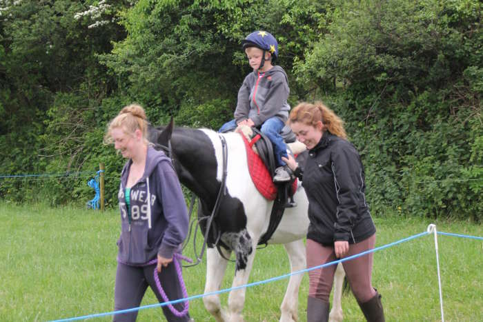 Photograph of two girls leading child on pony ride at Kinsale races