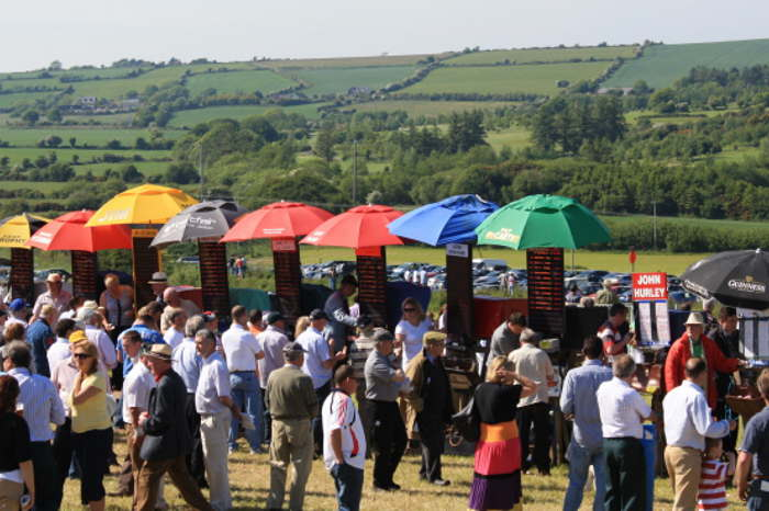 Photograph of bookies and punters with with umbrellas at Kinsale Point to Point