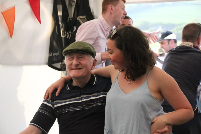 Photograph of old gentleman and young girl enjoying beer tent at Kinsale Point to Point