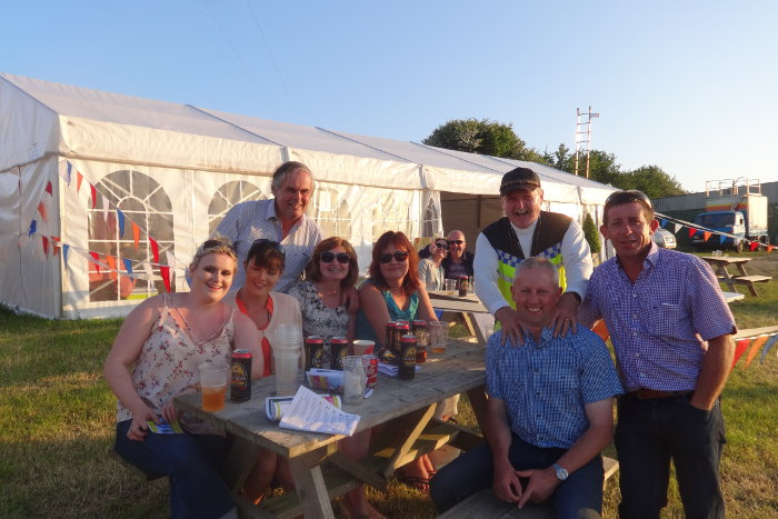 Photograph of people at picnic table with racecard Kinsale Point to Point